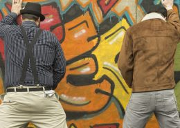 urine repellent paint on a wall where to men are taking a leak against
