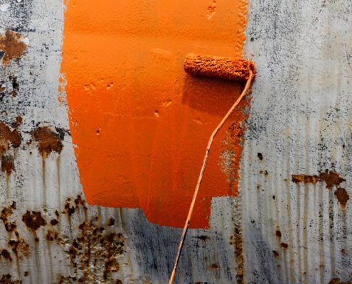 steel corrosion protection coatings in orange applied on a rusty tank